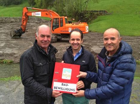 Der Projektleiter Urs Bollmann nimmt die Baubewilligung von Norbert Patt und Peter Reinle in Empfang.